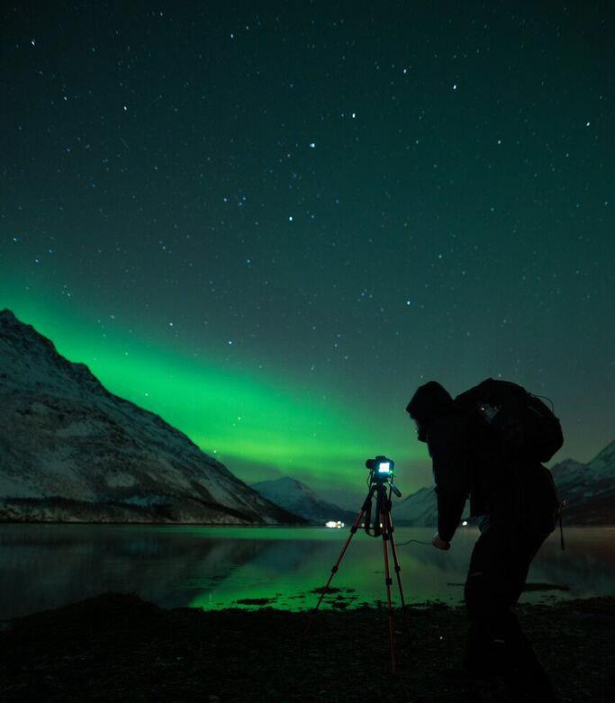 fotografo aurora boreale sul lago ghiacciato